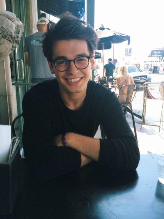 hombre lindo sonriendo con lentes en una mesa