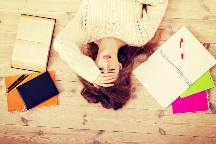 Chica recostada en el suelo rodeada de libros