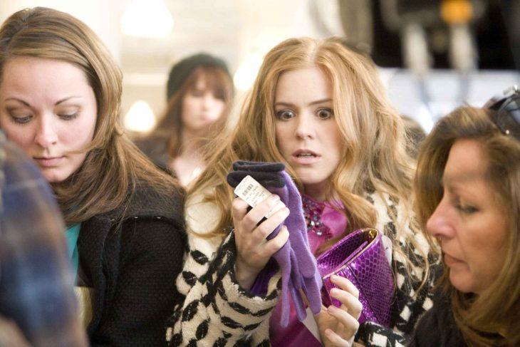 Escena de la película loca por las compras, chica intentando comprar unos guantes
