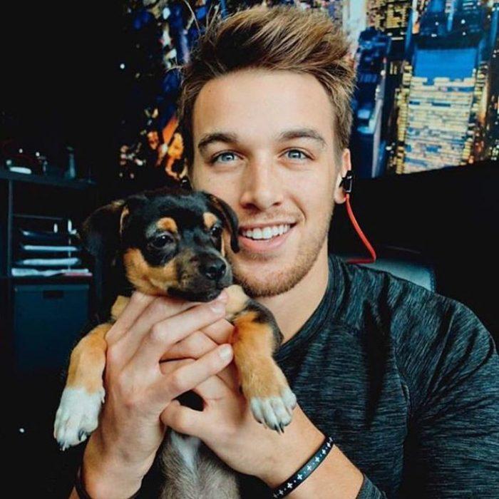 Chico sonriendo y sosteniendo a su cachorro