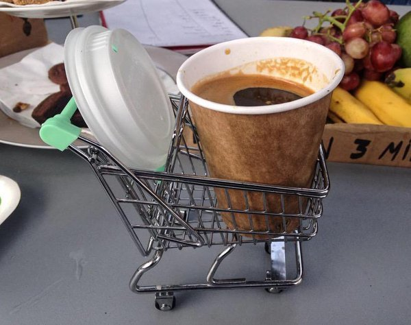 Café colocado en un mini carro de supermercado