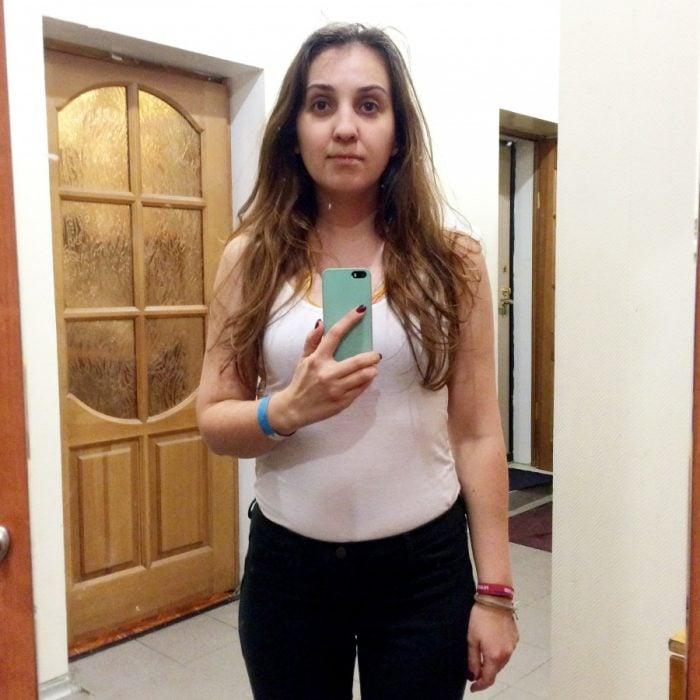 Chica parada frente al espejo viendo como luce en los probadores