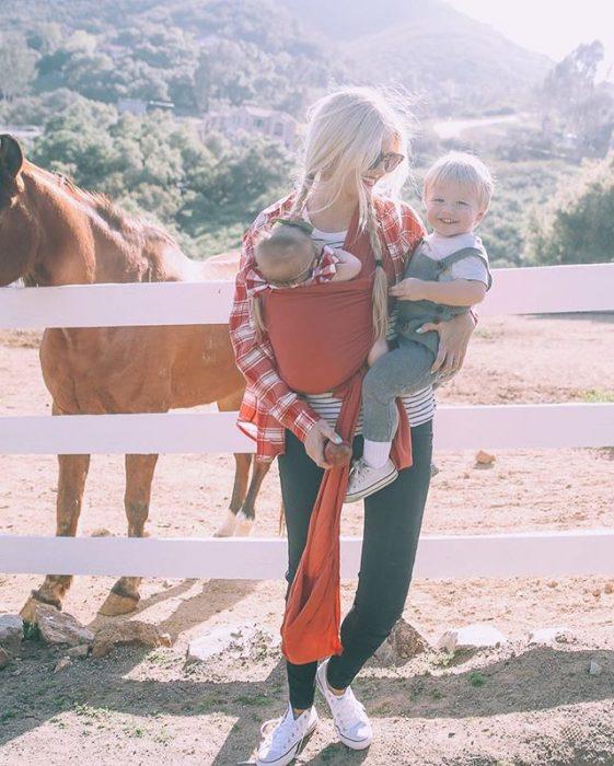 Chica cargando dos bebés frente a un establo