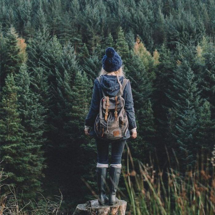 Chica parada frente a un bosque