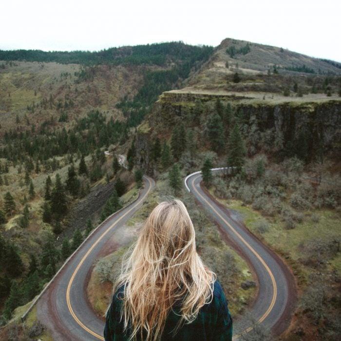 Chica en una montaña frente a una carretera