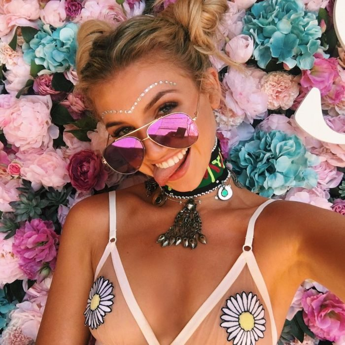 Chica recostada sobre una cama de flores usando dos buns despeinados