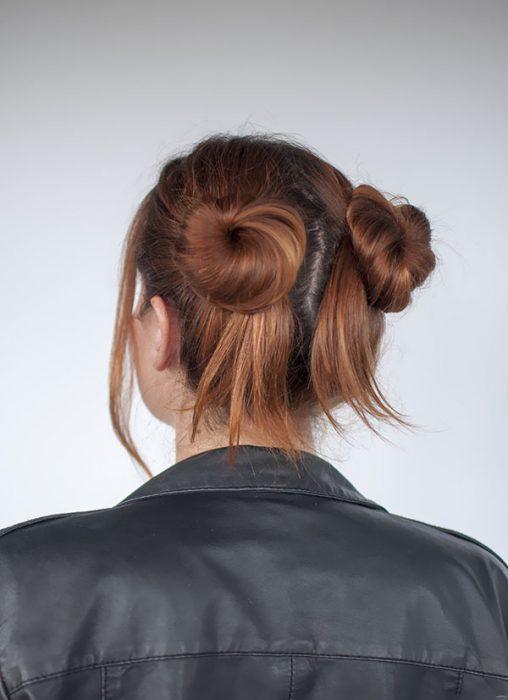 Chica con dos buns y algunos cabellos sueltos