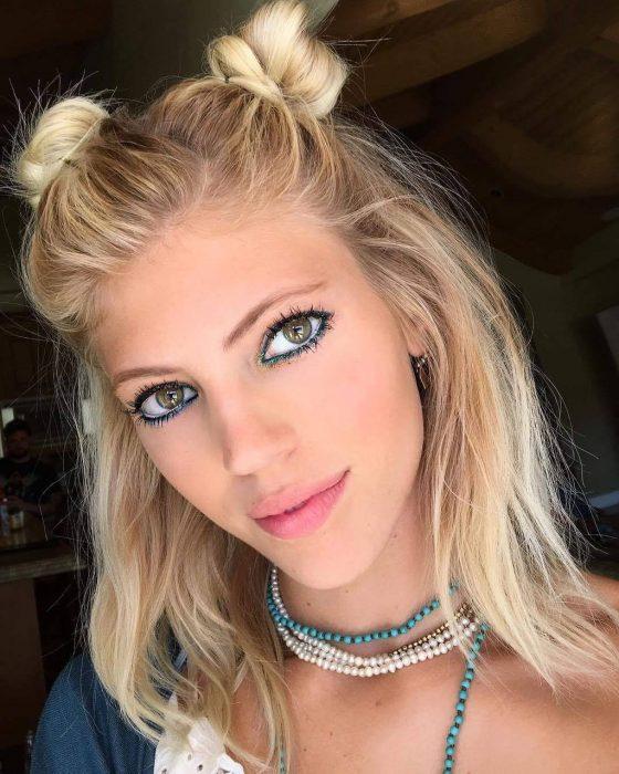 Chica con dos buns pequeños sujetados con la mitad del cabello