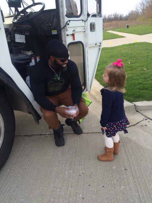 Niña regalándole un pastelillo al conductor del camión de basura