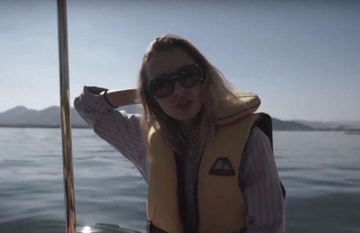 mujer rubia en unb barco con salvavidas