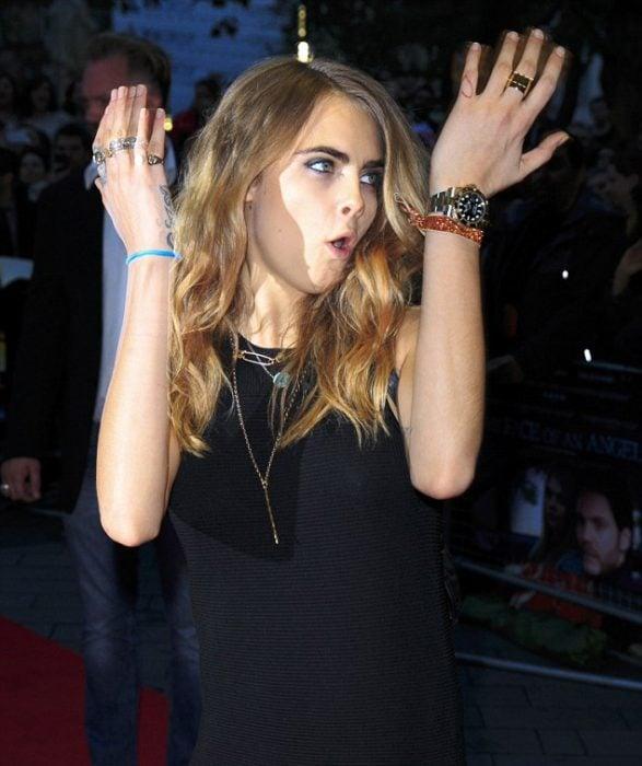 Cara Delevigne enojada levantando los brazos