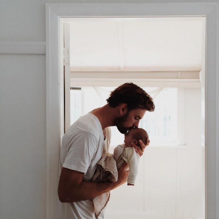 Chico con barba besando un bebé