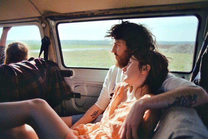 Chico con barba abrazando a su novia en una camioneta