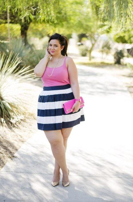 Chica plus size vistiendo una falda en color azul con blanco y una blusa color rosa