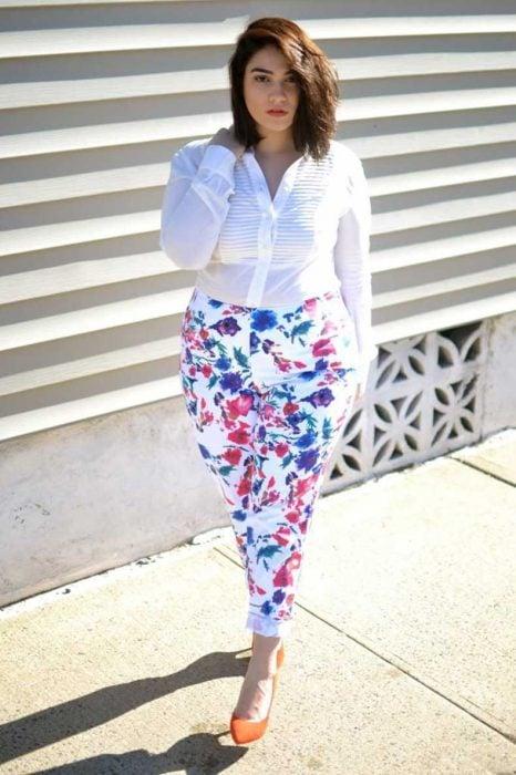 Chica plus size usando un pantalón con estampados y una blusa blanca