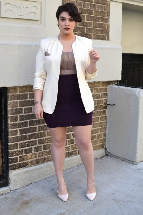 Chica plus size vistiendo un blazer balnco falda negra y blusa dorada