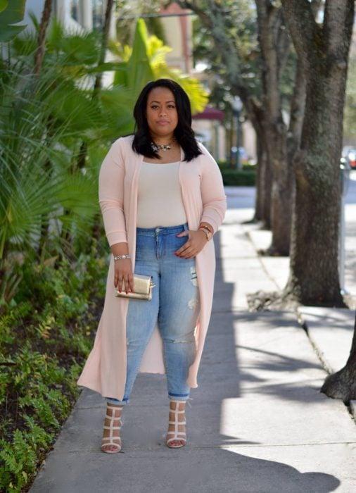 Chica pluz size usando una pantalón de mezclilla, blusa blanca y un súeter largo color rosa
