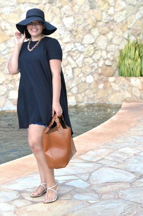 Chica pluz size vistiendo un bluson largo con short y sombrero