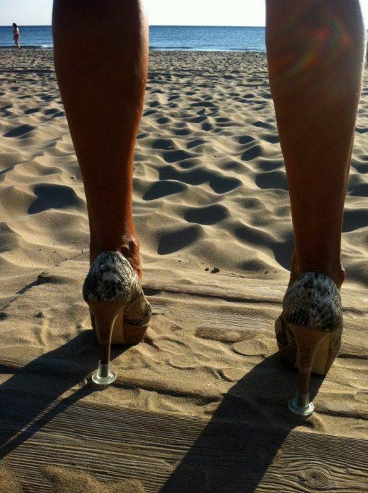 mujer con tacones en la playa