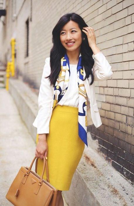 Chica usando un pañuelo con una blusa blanca y una falda amarilla