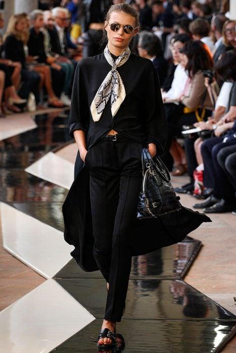 Chica usando un pañuelo con estampados mientras usa un traje color negro