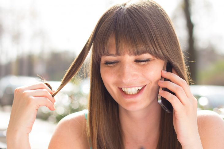 chica tocándose el cabello mientras habla por teléfono