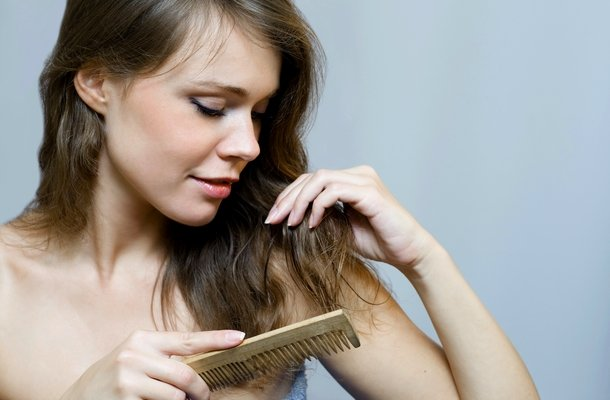 mujer cepillando cabello con peine