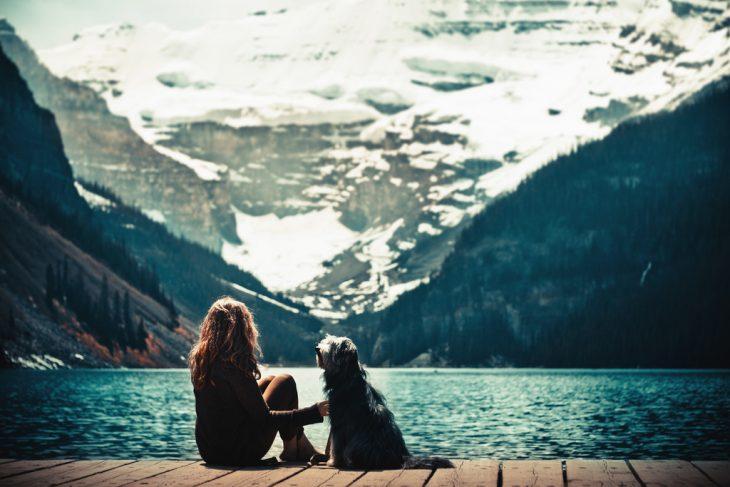 Chica a la orilla de un lago con su perro
