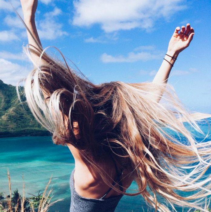 Chica bailando frente a la playa