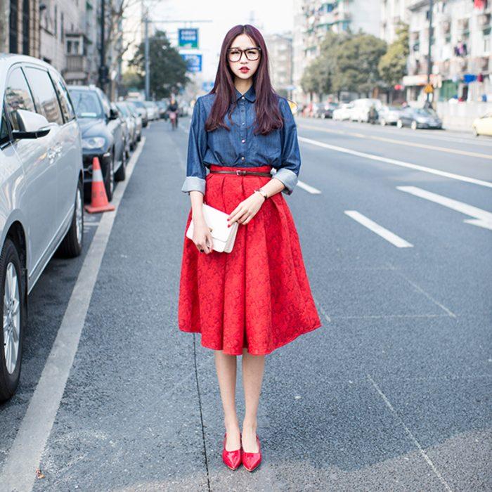 mujer en la calle con falda roja camisa azul y tacones rojo