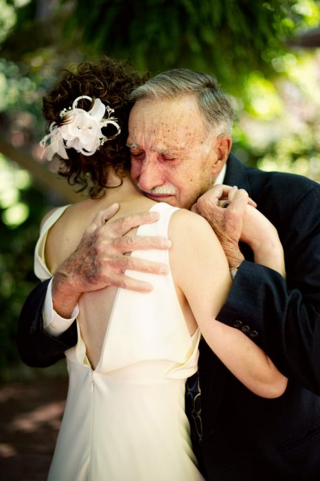 Chica el día de su boda abrazando a su abuelo