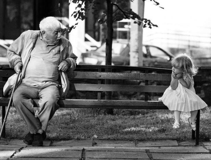 Niña sentada en una banca junto a su abuelo