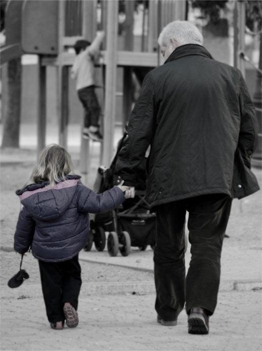 Abuelo caminando de la mano junto a su nieta