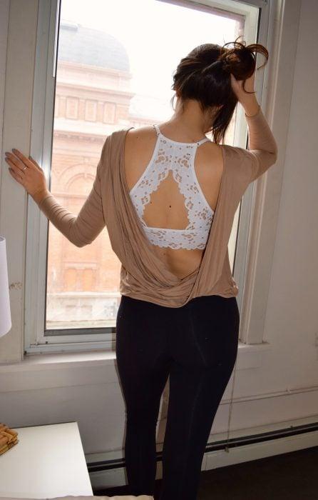 Chica mostrando la espalda de un bralette en color blanco