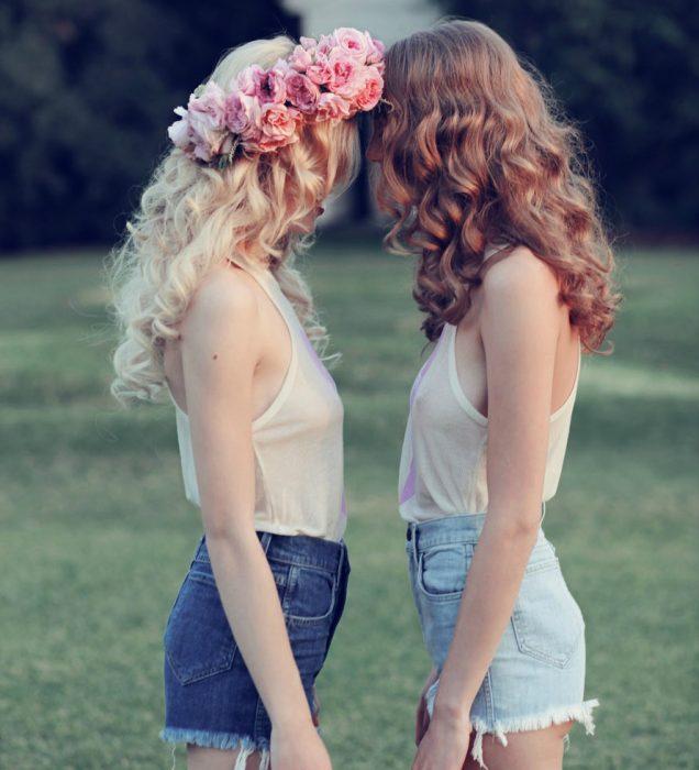 chica rubia con corona de flores en su cabeza y amiga enfrente