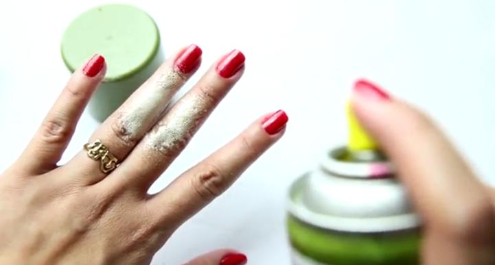 mano con uñas color rojo y spray de cocina