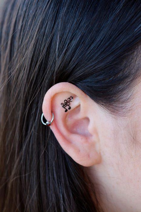 Chica con un tatuaje atrás de la oreja en forma de nota musical