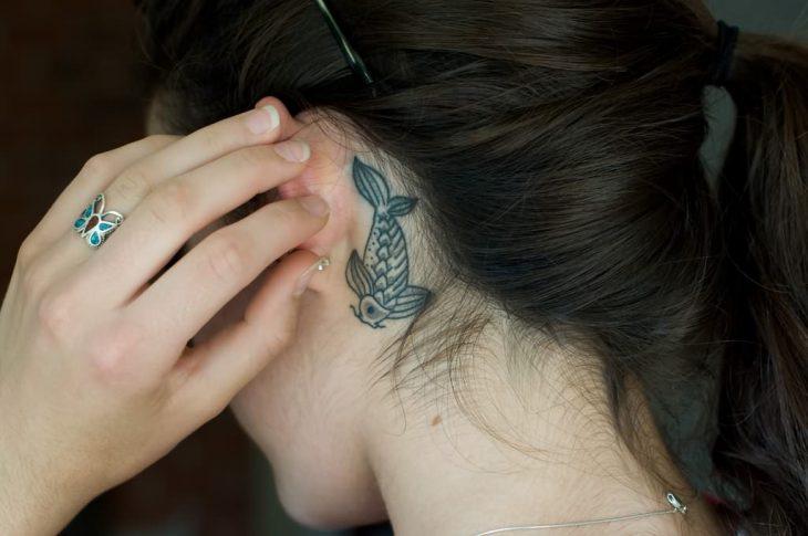 Chica con un tatuaje atrás de la oreja en forma de pez coi