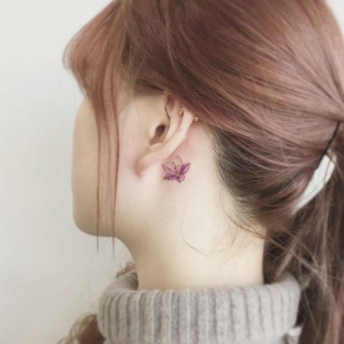 Chica con un tatuaje atrás de la oreja en forma de flor color rosa