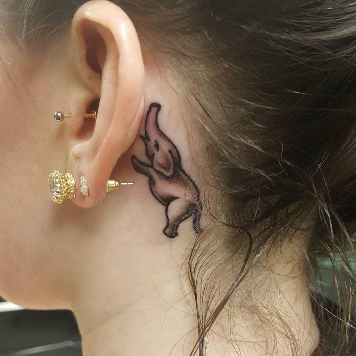 Chica con un tatuaje atrás de la oreja en forma de elefante