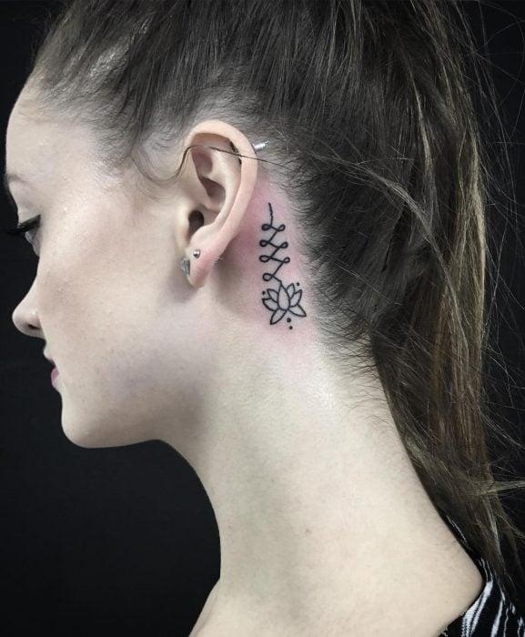 Chica con un tatuaje atrás de la oreja en forma de flor