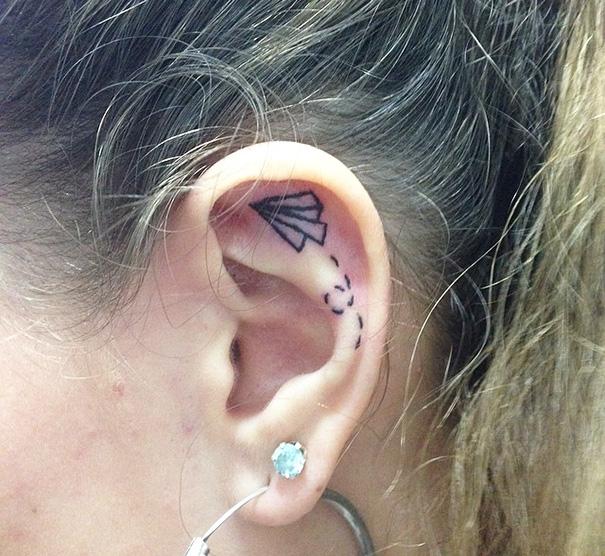 Chica con un tatuaje atrás de la oreja en forma de avión de papel