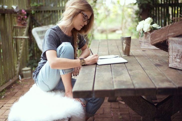 Chica sentada frente a una mesa escribiendo en una libreta