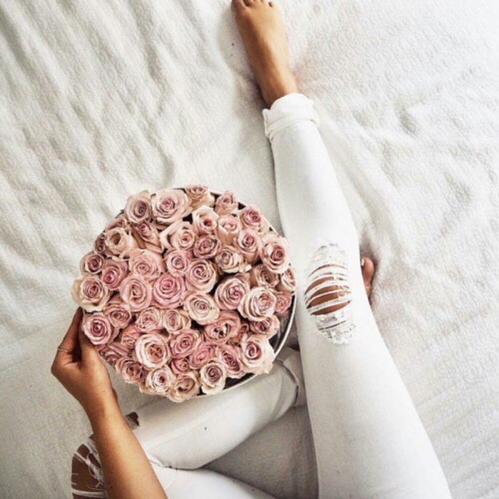 mujer con flores en la cama