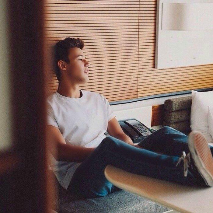 chico sentado con pies en la mesa voltea a la ventana