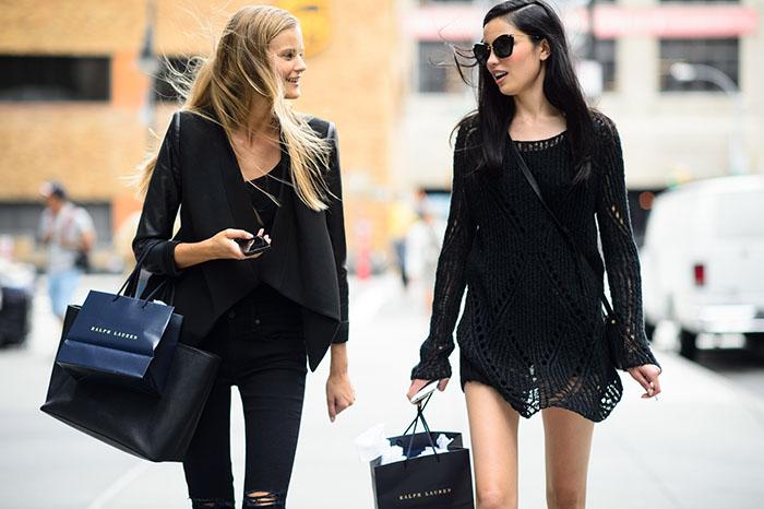dos mujeres en la calle caminando con bolsas de compras