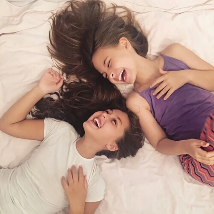 dos chicas en una cama riendo felices