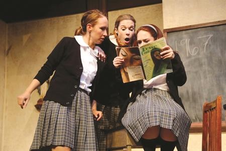 Chicas de una escuela católica viendo una revista