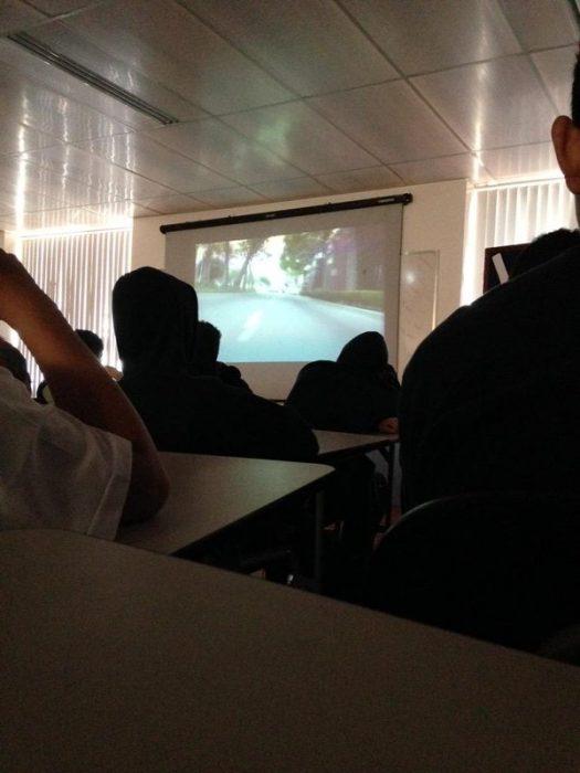 Chicos viendo una película en clase