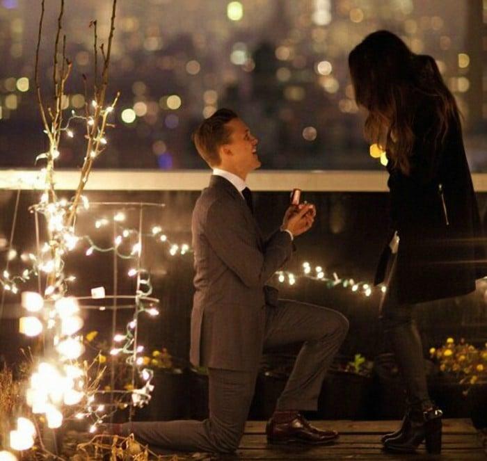 hombre se inca proponiendo matrimonio a mujer
